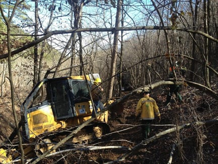 Extreme winter weather conditions, paired with steep, forested, challenging terrain - with few access routes - framed the entire search mission. This image, courtesy of Arkansas Forestry Commission, captures the scene near the plane's final resting place. Notice the special equipment needed to create a path, the heavy woods, ice storm debris still covering the forest floor, and terribly steep mountainside. This area is 26 miles away from Jake's last check-in point, near Oden.