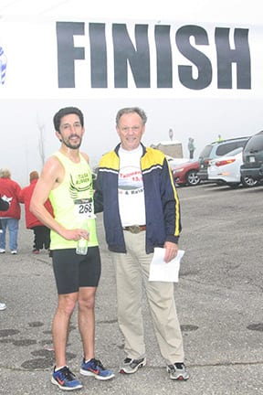 Race Director Dale Powell congratulated first-place finisher Matt Aguero, who completed the 1/2 marathon with an impressive time of 1 hour, 29 minutes, 54 seconds.
