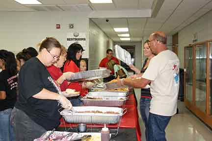 Arvest and Country Express joined together to offer a fish-fry fundraiser for the Bearcat Foundation to benefit the Mena Marching Bearcat Band. Above, Eugene Taff of Country Express, is shown delivering a tray of fresh fried fish as Jennifer Graves, of Arvest, assists with serving.